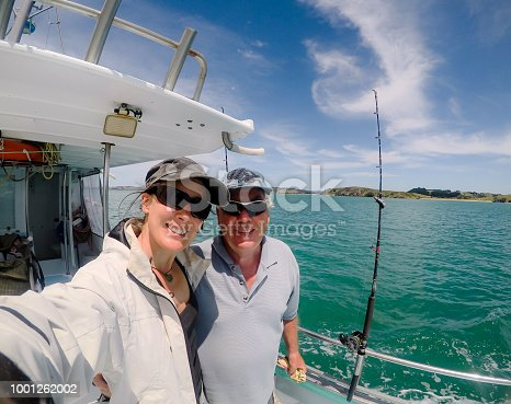 Selfie: father and daughter male and female caucasian tourists on fishing charter vessel in Far North District, Northland, New Zealand, NZ