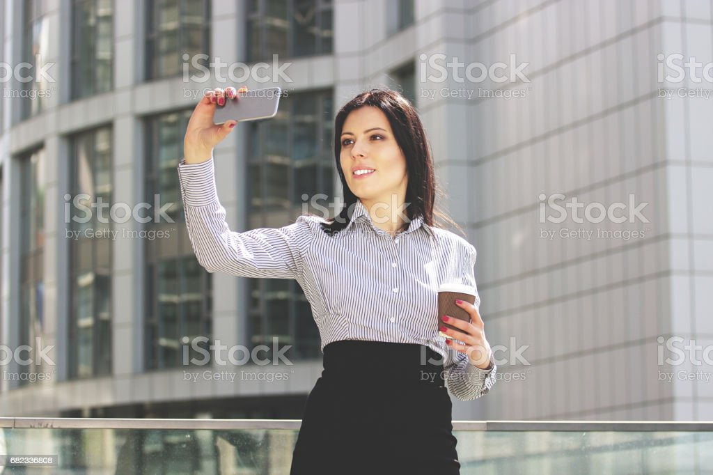 Selfie for colleagues. Beautiful and happy business woman in smart casual wear taking a selfie against office building while drinking coffee. zbiór zdjęć royalty-free