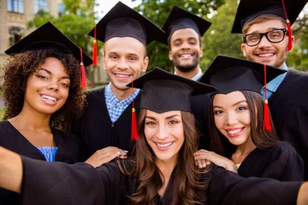 Selfie for memories. Six with cheerful graduates are posing for selfie shot, attractive brunette lady is taking, wearing gowns and mortar boards, outside on a summer day stock photo