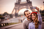 Photo of happy smiling couple making selfie in front of the Eiffel Tower in Paris, France