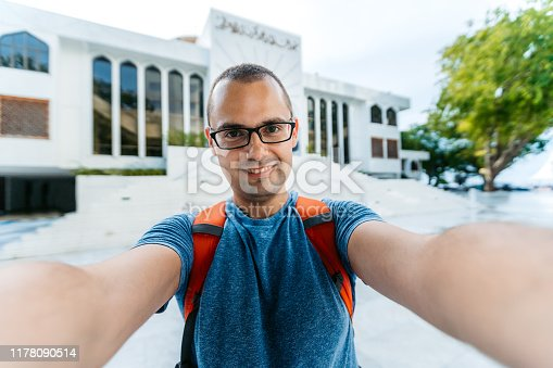 Young Caucasian man making a selfie in front of Grand Friday Mosque Male, Maldives.