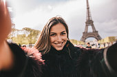 Beautiful young woman taking selfie in front of \neiffel tower in Paris