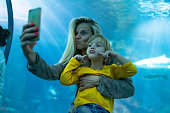 Mother and son is taking selfie with fish in public aquarium