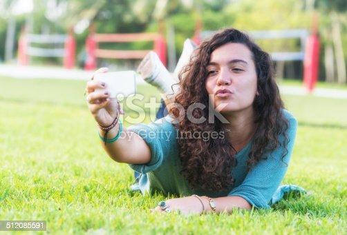 istock Selfie of a beautiful Hispanic girl lying on the grass. 512085591