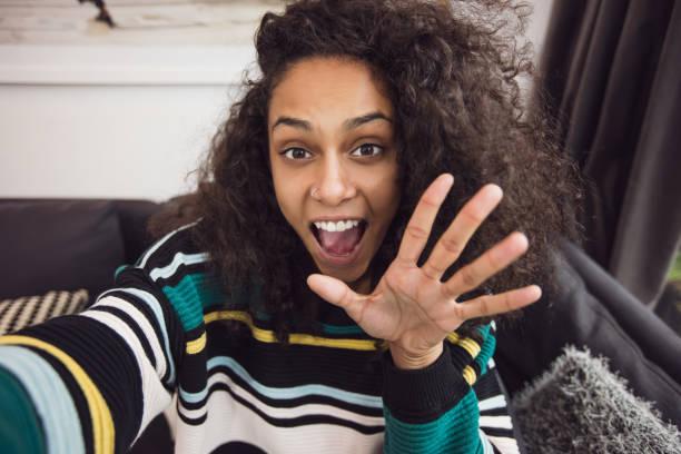 Selfie of charming woman waving to camera stock photo