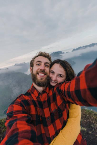 Selfie of  couple standing on Reinebringen mountain on Lofoten Island stock photo