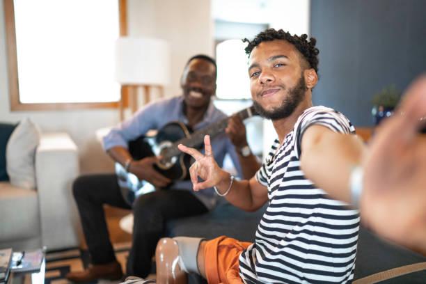 リビングルームで音楽を演奏する父と息子の自分撮り - disabilitycollection ストックフォトと画像
