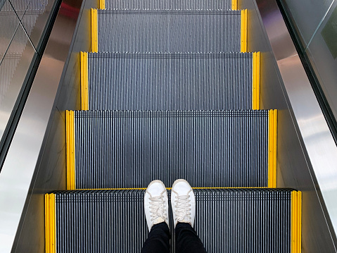 Selfie of feet in white sneakers shoes standing on escalator in shopping mall or modern office