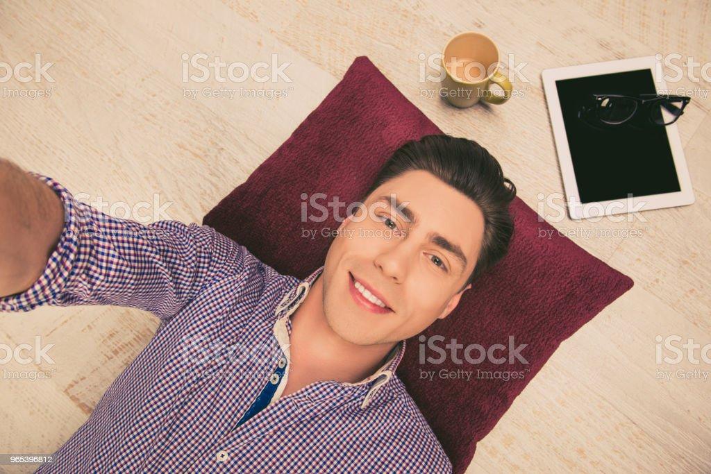 Selfie de bel homme heureux couché sur le sol avec tablette et tasse de thé - Photo de A la mode libre de droits