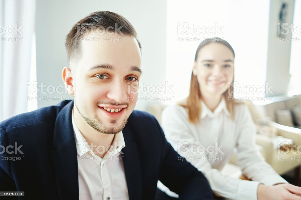 Selfie of smiling young businessman looking at camera at formal meeting, his defocused female colleague in the background royalty-free stock photo