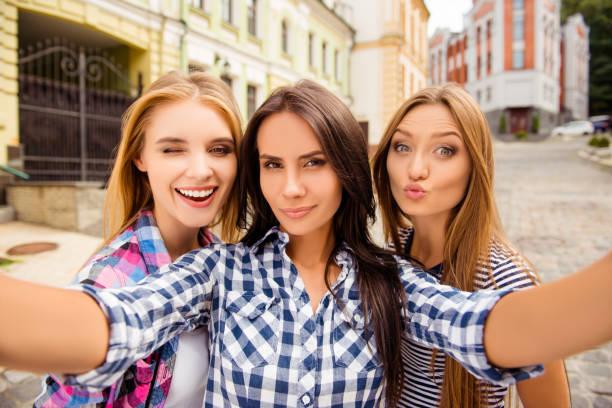 selfie von drei schönen freundinnen schmollend und zwinkert - happy weekend bilder stock-fotos und bilder