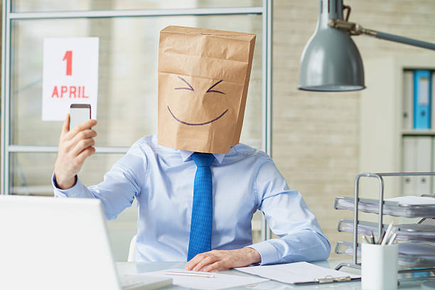 Selfie on Fool's day Office worker wearing paper bag taking a selfie with smart phone on April fool's day april fools day stock pictures, royalty-free photos & images