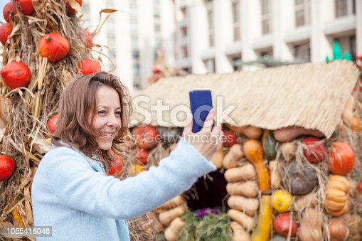 Woman is photographed on the background of pumpkins