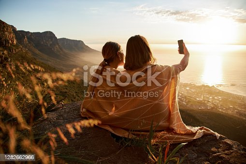 Rear view of young couple taking selfie on the mountain top.