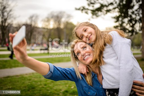 Mother and daughter making a selfie at the park.