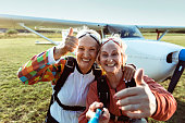 Close up of two senior friends taking a selfie before skydiving