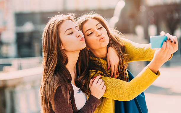 Selfie Two beautiful girls taking a selfie and making strange faces. puckering stock pictures, royalty-free photos & images