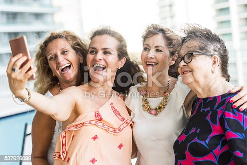 Smiling  caucasian mature women and their senior mother looking at the smart phone taking a selfie