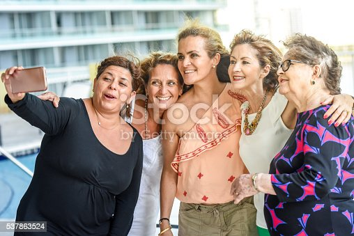 Smiling hispanic and caucasian mature and senior women looking at the smart phone taking a selfie