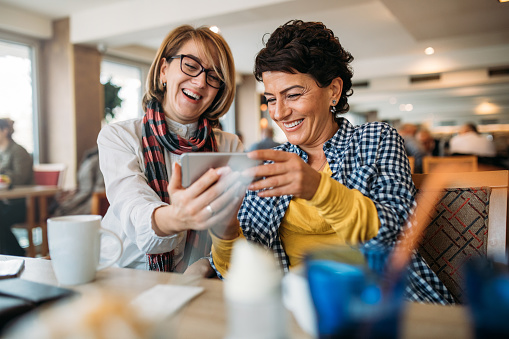 Photo of two women take selfie with smart phone