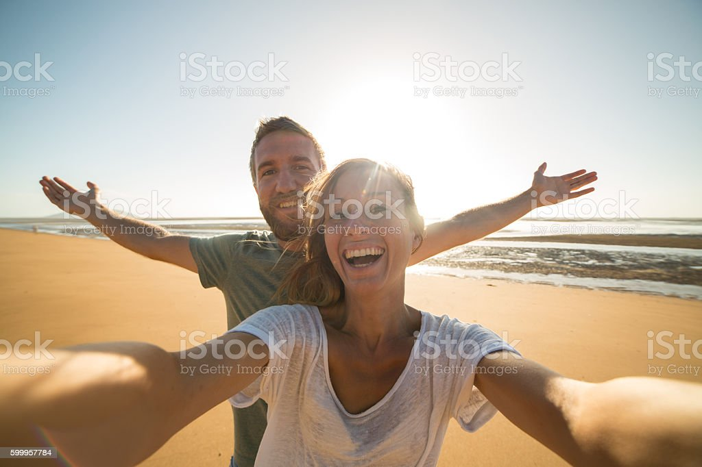 Selfie portrait of young couple on beach at sunset stock photo