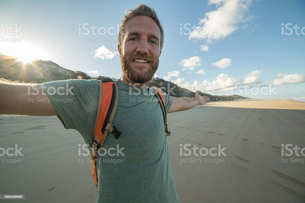 Selfie portrait of young man on beach at sunset stock photo
