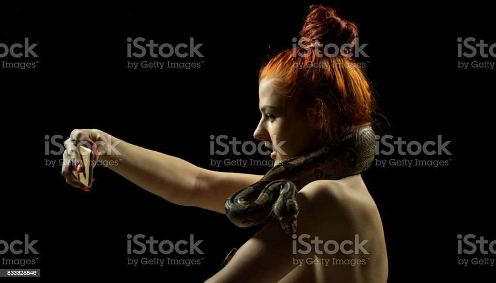 A selfie portrait with mobile. Colombian Boa and woman. Tropical brown constrictor curled on her body. Snake skin with yellow and black spots on a black background stock photo