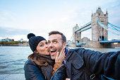 Happy couple making selfie with Tower Bridge in London. Winter season.