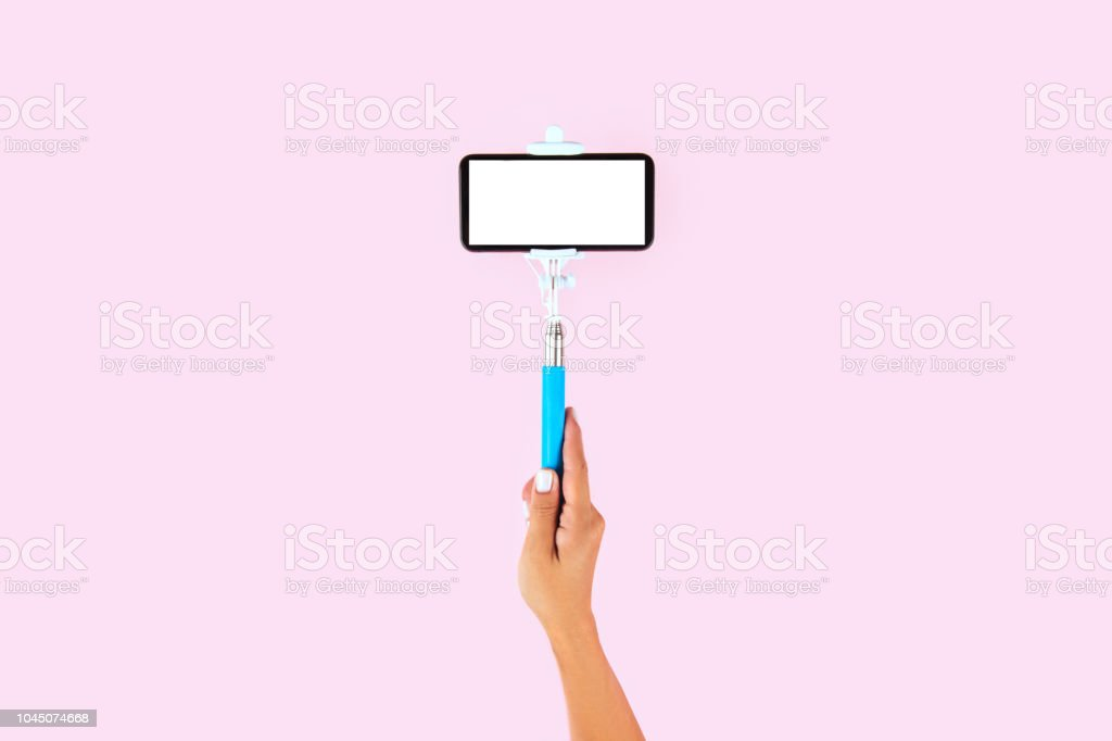 Selfie stick and white smart phone on pink background stock photo