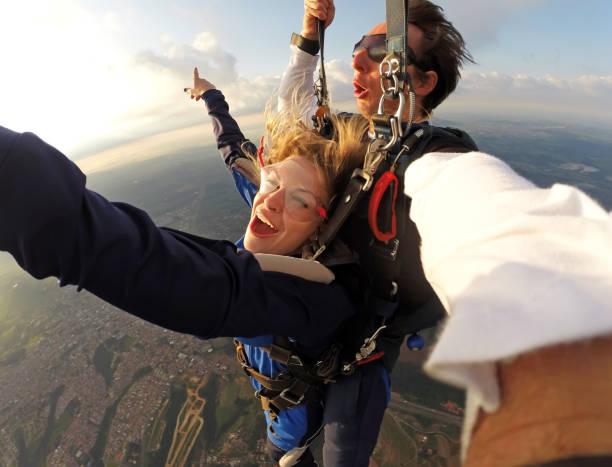 selfie tandem parachutespringen met mooie vrouw - adrenaline stockfoto's en -beelden