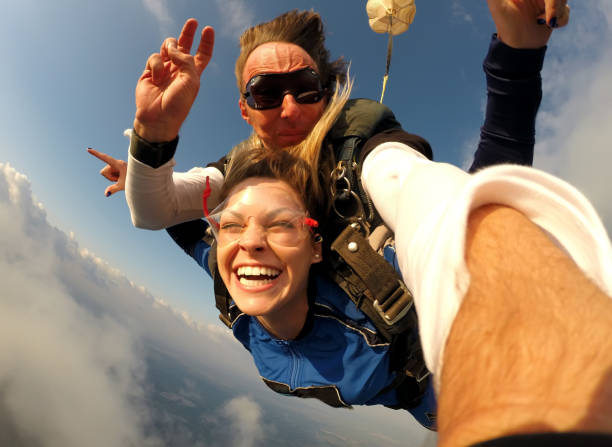 Selfie tandem skydiving with pretty woman stock photo