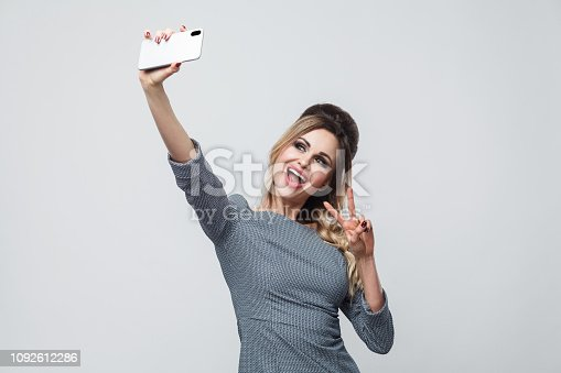 istock Selfie time! Happy beautiful blogger teenager wearing in grey dress with pigtail on head standing, showing v sing with toothy smile and making selfie. 1092612286