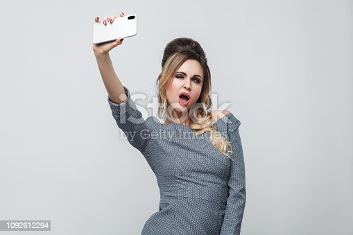 istock Selfie time! Happy beautiful blogger young girl wearing in grey dress with pigtail on head standing, winking with sexy open mouth and making selfie. 1092612294