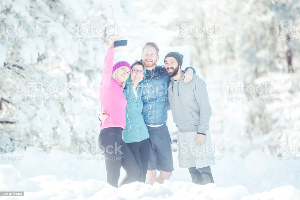 Four friends and also sportspeople are standing on mountain and...