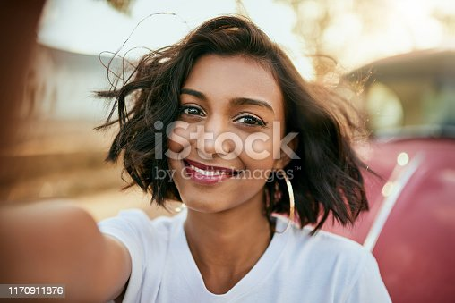 Cropped portrait of an attractive young woman standing against her car and taking a selfie alone during a day out
