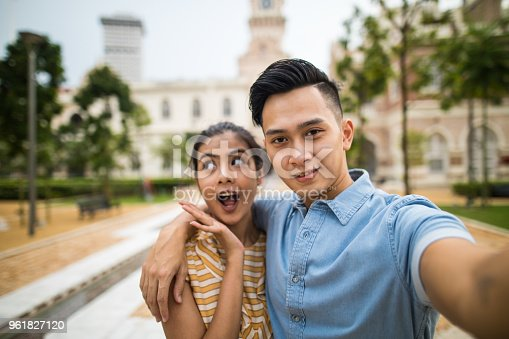 Young beautiful heterosexual couple taking a selfie in front of the Sultan Abdul Samad Building, Kuala Lumpur, Malaysia