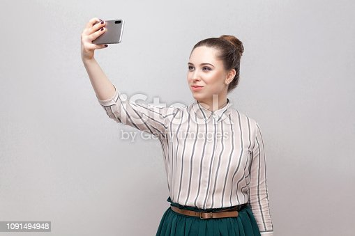 640046924 istock photo Selfie time! Portrait of happy attractive blogger woman wearing in striped shirt standing, holding phone and making selfie. 1091494948