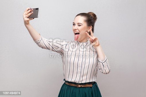 640046924 istock photo Selfie time! Portrait of happy foolish joyful attractive blogger woman wearing in striped shirt standing, winking and showing tongue and making selfie. 1091494974