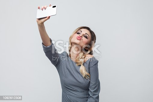 istock Selfie time! Selfportrait of happy beautiful blogger teenager wearing in grey dress with pigtail on head standing, sending air kiss and making selfie. 1092612308