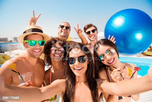 Selfie time! Six cheerful friends in fashionable different swim wear and sun protecting eyewear, caps, with drinks are posing for a selfie photo, that brunette lady is taking, beaming smiles, sunshine