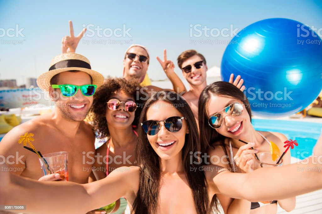 Selfie time! Six cheerful friends in fashionable different swim wear and sun protecting eyewear, caps, with drinks are posing for a selfie photo, that brunette lady is taking, beaming smiles, sunshine stock photo