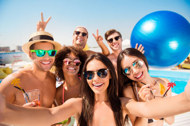 Selfie time! Six cheerful friends in fashionable different swim wear and sun protecting eyewear, caps, with drinks are posing for a selfie photo, that brunette lady is taking, beaming smiles, sunshine - foto stock
