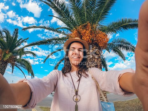 Young beautiful caucasian woman making selfie under the palm tree.