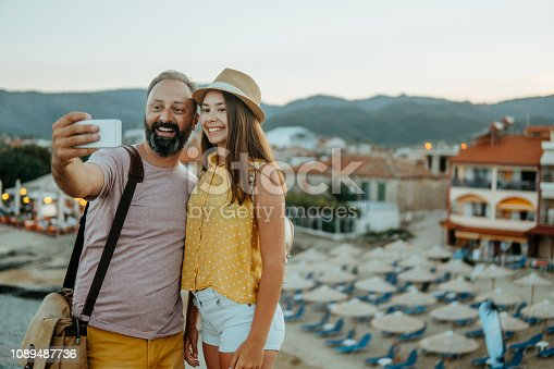 Photo of father with his daughter taking selfie on the travel