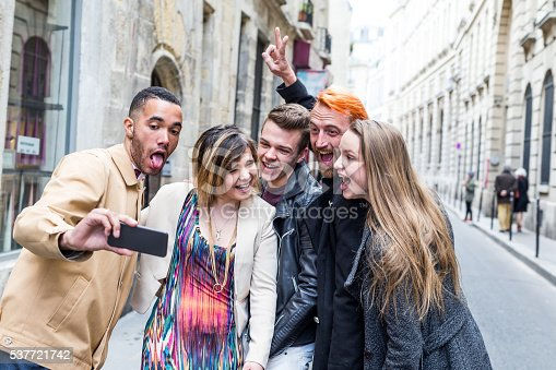 Group of friends taking selfie on the streets of Paris, France.