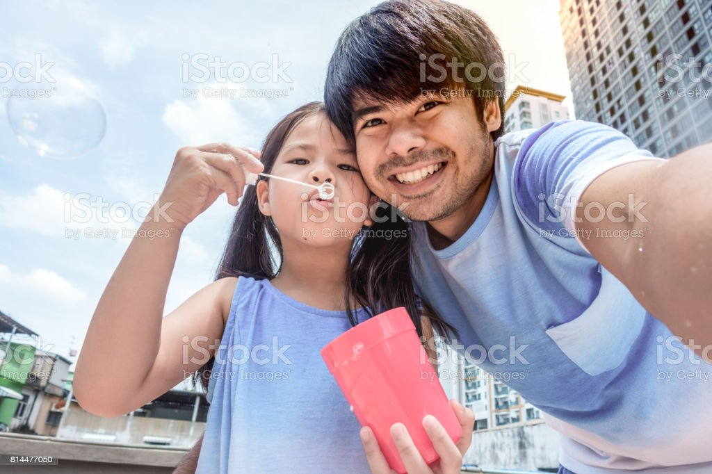 Selfie with my daughter playing bubble on a rooftop at home stock photo