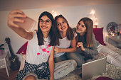 Smiling teenage girls spending time together and taking a selfie