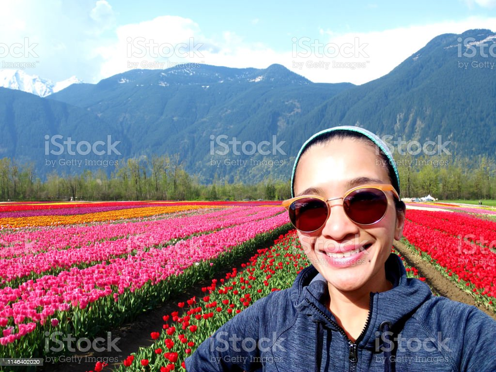 One young adult woman taking a selfie in a cultivated tulip field...