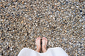 Selfie Young Woman of Feet in Fashion Shoes on Stones Floor. Beautiful Girl Standing is Foot & Slim Legs Seen from Above on Road Street. Flat Shoe (Sandal) on Cement Layoknok Background, Top View.