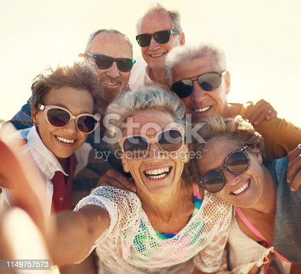 Cropped shot of a group of senior friends taking selfies while enjoying their day out on the beach